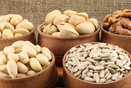 Abstract view of the mixture of nuts in a round wooden form on the background of natural fabrics photo