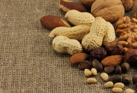 Abstract view of the mixture of nuts on the background of natural fabrics photo