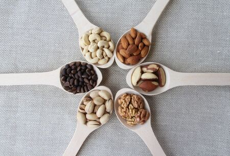 Abstract view of a wood spoon with mixed nuts on a background of natural fabrics photo