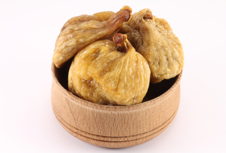 pectin: Dried figs in a wooden round shape on white background