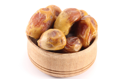 Dates with stones in a wooden round shape on a white background photo