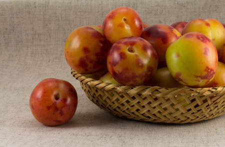 wickerwork: Plums wickerwork oval shape on the background of natural fabrics