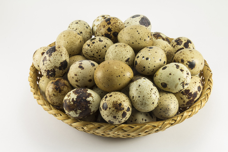 oval shape: Type of quail eggs in a wicker oval shape on a white background