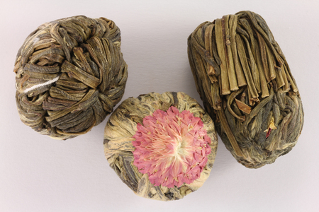 globosa: Flowering tea or blooming tea  consist each of a bundle of dried tea leaves wrapped around one or more dried flowers. Stock Photo