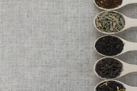 lemongrass tea: Assortment of different types of tea in a wooden spoon on a background of gray natural fabric