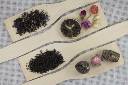 lemongrass tea: Assortment of different types of tea on a wooden kitchen spatula on a background of gray natural fabric