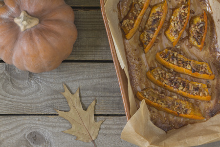 Authentic view of a pumpkin baked with slices of honey and walnuts on old wooden background