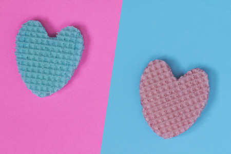 Creative heart from an edible wafer in pastel pink and blue colors. Abstraction. Template. Top view.
