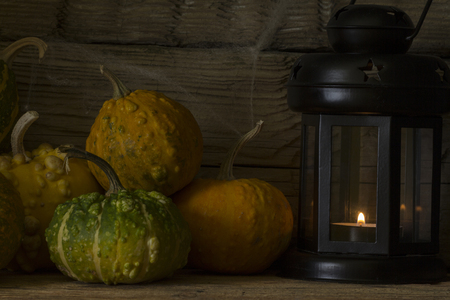 Abstract view of decorative pumpkins with a lantern and a candle on a wooden background. Halloween. Top view.