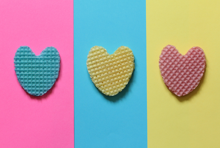 Creative heart from an edible wafer in pastel pink, blue, yellow colors. Abstraction. Template. Top view. Stock fotó