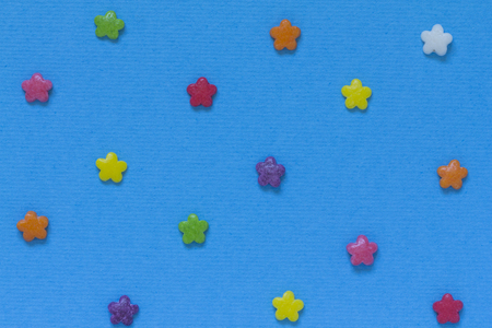 Multicolored candy in the form of flowers on a blue background. Template. Macro.