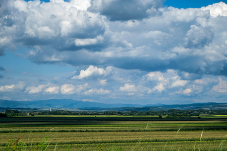Farm Field with Cloudscape and Mountains Stock Photo