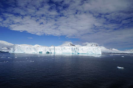 This is summer in Pleneau Island, Antarctic Peninsula. There are penguins, whales, icebergs, ice floes, glaciers, oceans, radioactive clouds and sunlight. Stock Photo