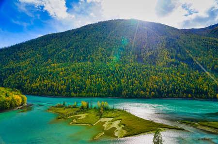 Wolong Bay of Kanas Lake. Crystal blue river, small sandbar. Green tree hills. The natural beauty of the paradise. Kanas Nature Reserve. Xinjiang Province, China. Sep. 2018