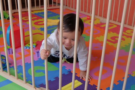 little cute boy playing and crawling in playpen on alphabet puzzle mat