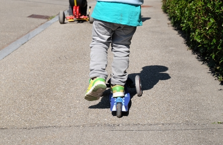 Close up of feet riding scooter outdoor. Kid learning to ride scooter. Imagens