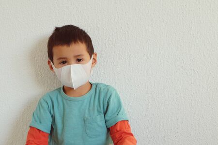 Young mixed race Thai-Swiss child boy wearing a mask isolated on white background. Virus protects concept idea. Coronavirus protection. Stock Photo