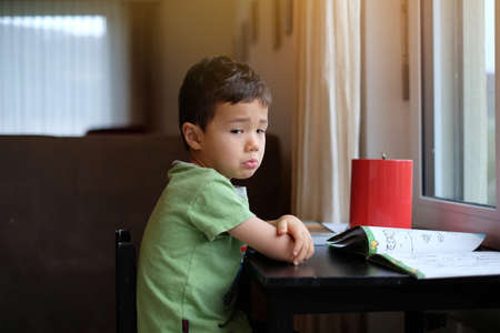 Portrait of Sad little kid boy sitting on the black chair next to the window and does not want to play, warm light tone.