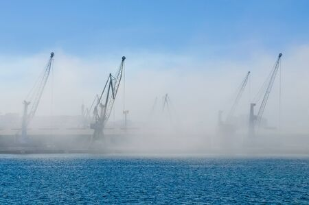 Dockyard cranes in mist with blue sky and water in the foreground