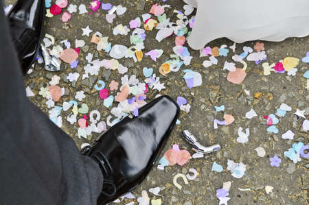Overhead view of a bride and grooms feet with confetti on the floor Stock Photo