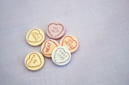 Love heart sweets against a white fabric background photo