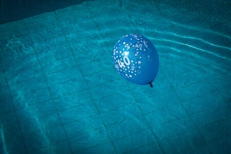 Blue balloon with numbers on in swimming pool