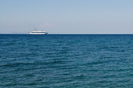 White ferry on horizon in clear blue sea