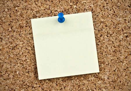 Blank paper note pined on cork board