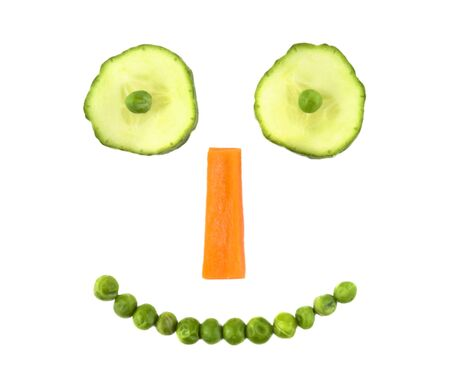green smiley face: Vegetable smiley made of cucumber, carrot and peas isolated on white Stock Photo