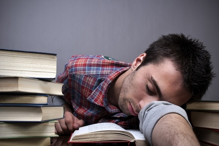 Exhausted young man sleeping with bunch of books around him