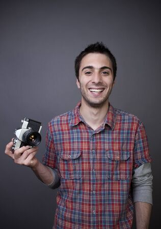 Smiling young man posing with retro photo camera on gray background photo