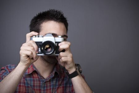 Young man with retro photo camera posing on gray background with copy space photo
