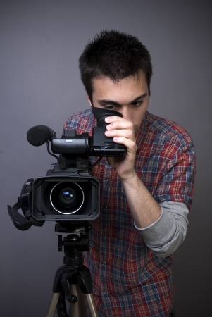 Young man with professional video camcorder on gray background photo