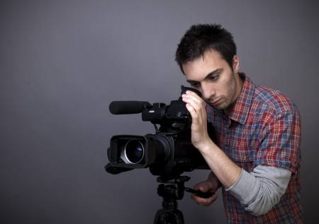 Studio shot of young man with video camcorder on gray background with copy space