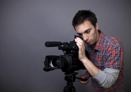 Studioaufnahme des jungen Mannes mit Video-Camcorder auf grauem Hintergrund mit Kopie Raum Standard-Bild - 13522006