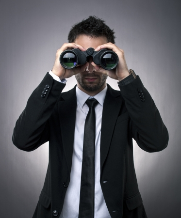 marketing research: Young businessman looking through binoculars - market research concept