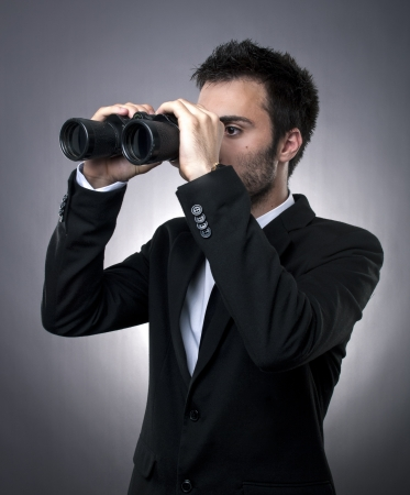 Young businessman in black suit looking through binoculars - market research concept
