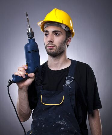 Studio shot of young construction worker with electric drill photo