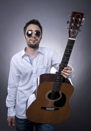 Studio shot of young man with sunglasses and acoustic guitar on gray background Stock Photo