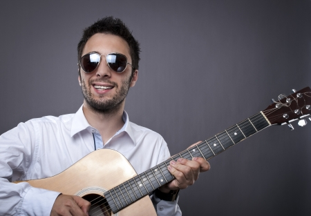 Smiling man with sunglasses playing acoustic guitar photo