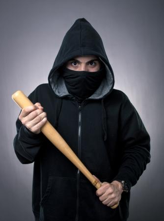 gang: Studio shot of  young hooligan with baseball bat on gray background