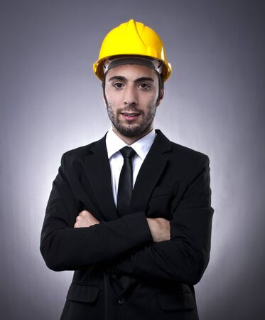 Young investor in black suit with yellow construction helmet posing with arms crossed