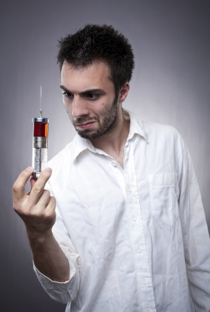 Young medical worker with weird facial expression  looking at huge syringe photo