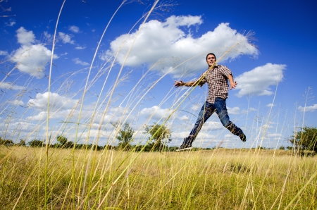 Young man jumping on dry meadow  against blue sky