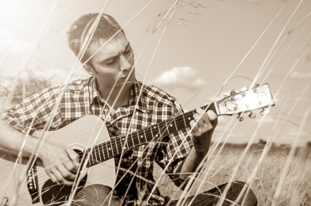 Young musician playing guitar among high grass - monochrome photo
