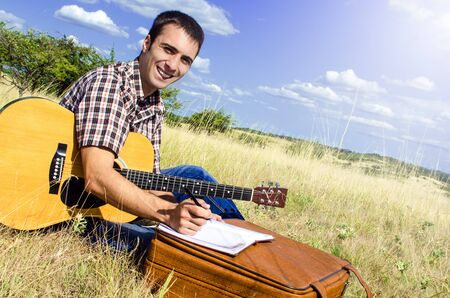 man playing guitar: Cheerful traveling musician writes a song on sunny day Stock Photo
