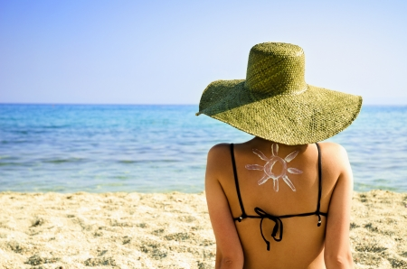 Woman on beach with sun symbol on her back - UV protection concept Stockfoto