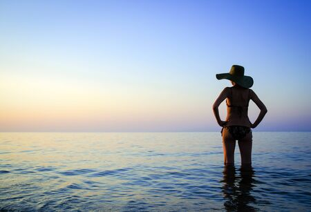 Relaxed woman standing in shallow water and watching the sunset Stock Photo
