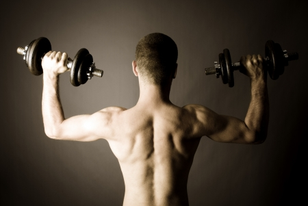 Rear shot of muscle man with two dumbbells - monochrome