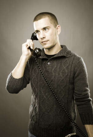 Studio shot of attractive man with old phone - retro style Stock Photo